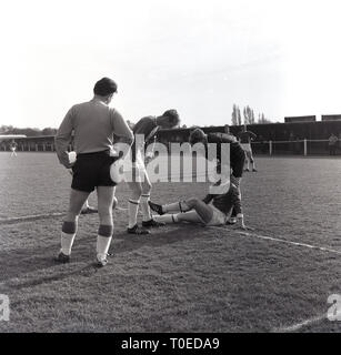 1964, amateur football match, referee with injured player on ground, England, UK. - Stock Image