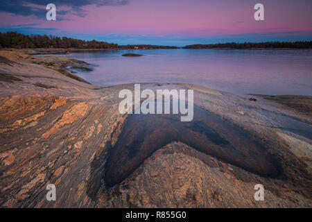 Beautiful winter evening landscape by the Oslofjord, at Oven in Østfold, Norway. The blue part on the sky is the shadow of the earth. - Stock Image