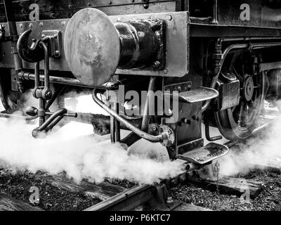 Monotone close frontal shot of a steam locomotive at the Mid Suffolk Light Railway, showing buffer and couplings emerging from light steam - Stock Image