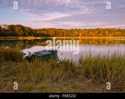 Salt Pond, Eastham MA Cape Cod, Massachusetts, USA solitary wooden boat moored fall color autumn colours reflections - Stock Image