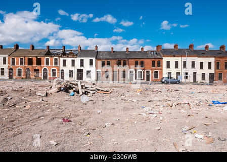 A long row of derelict houses in a street boarded up with steel plates in front of an area where houses have been - Stock Image