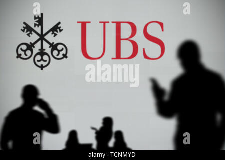 The UBS logo is seen on an LED screen in the background while a silhouetted person uses a smartphone in the foreground (Editorial use only) - Stock Image