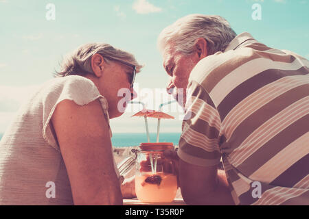 man and woman adult aged 60 years old drinking healthy fruit juice froma vase glass outdoor in the terrace. nice view and beautiful people. Vintage re - Stock Image