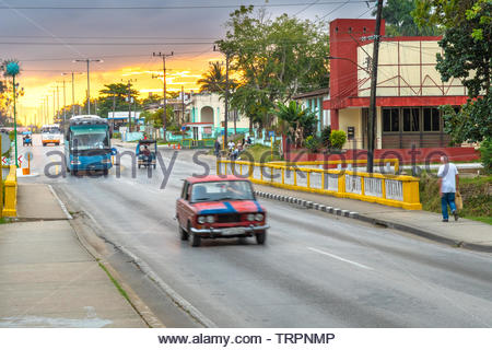 A red LADA car driving in the morning. There is a dramatic-sky sunrise in the Central Road which traverse the city from one point to the other. There - Stock Image