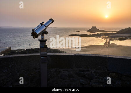 A seaside telescope looks out over an island and sunset at St Malo, Brittany, France - Stock Image