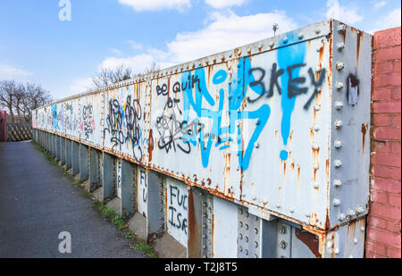 Spray paint grafitti on an old rusting iron railway footbridge on a footpath in Woking, Surrey, south-east England, UK - Stock Image