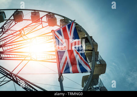 Union Jack flag with large ferris wheel in the backgound - Stock Image