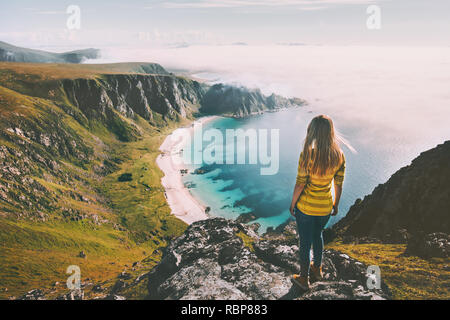 Summer travel woman tourist standing alone on mountain top over sea beach active lifestyle hiking adventure vacations in Norway outdoor - Stock Image