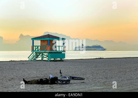 Man sleeping next to his bicycle on Miami's South Beach at dawn with a life guard's stand and a cruise ship - Stock Image