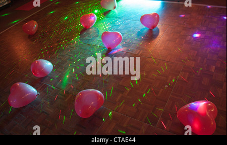 Balloon hearts on a dance floor in a club - Stock Image