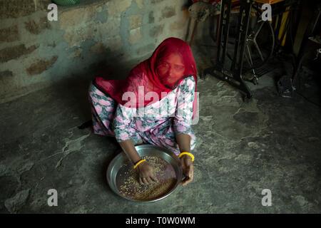A Muslim woman wearing a veil prepares millet in her house. Kakani village, Jodhpur, Rajasthan, India. - Stock Image