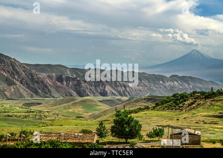 View of the mountain village against the background of Gegham ridges and the silhouette of mount Ararat, covered with haze and layered clouds covering - Stock Image