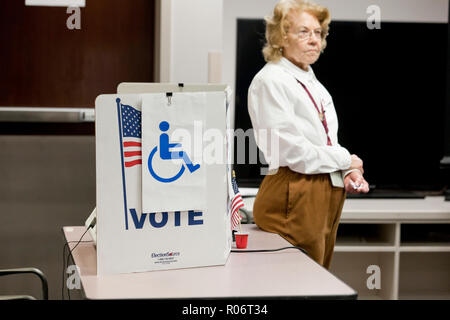 A poll worker (election official) awaits to assist any disabled voters - Virginia USA - Stock Image