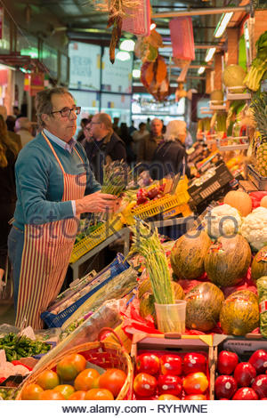 Stall holder arranging produce at Triana Market Seville - Stock Image