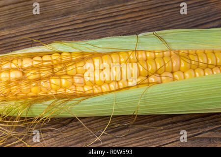 Close-up of corn cob in green husk. Zea mays. Beautiful ripe corncob detail. Golden maize grains, silks, thin leaves. Natural brown wooden background. - Stock Image