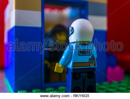 Poznan, Poland - February 10, 2019: Lego Police officer with helmet standing in front of a building entrance with closed door. Man hiding inside the h - Stock Image