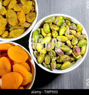 Selection of Healthy Snacks in White Bowls on a Table Top, Pistachio nuts, sultanas and Soft Dried Apricots, looking down with No People. - Stock Image