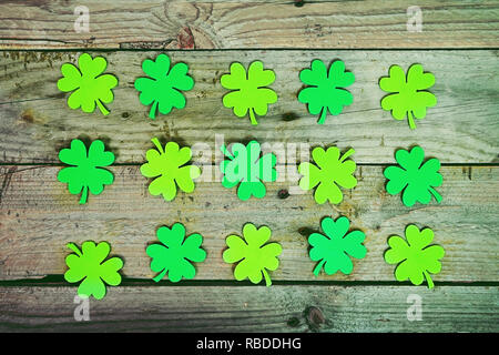 Beautiful close-up flat of many irish shamrocks, feast clovers, in a row that remind luck or Saint Patrick's Day with wooden tables as background - Stock Image