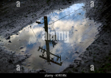 The reflection of a nearby powerline pole can be seen in a puddle of water. - Stock Image