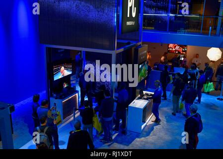 Attendees trying out demos of computers, augmented reality experience with Magic Leap One, video games, 5G at Intel booth at CES, Las Vegas, USA. - Stock Image