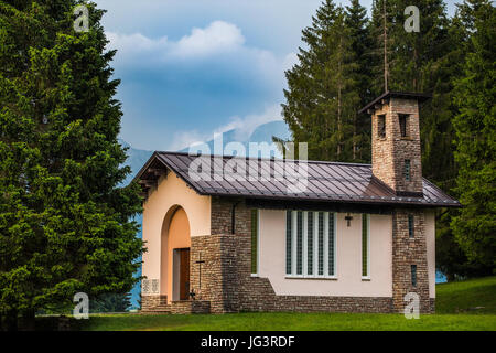 Christian church on a meadow near forest with mountains behind it. - Stock Image