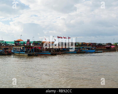 Tourist boats moored at side of Tonle Sap lake for trip to Kompong Phluk a stilted village on the lake side Siem Reap Cambodia Asia - Stock Image