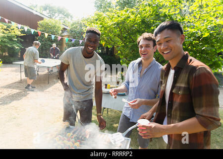 Portrait smiling male friends enjoying summer backyard barbecue - Stock Image