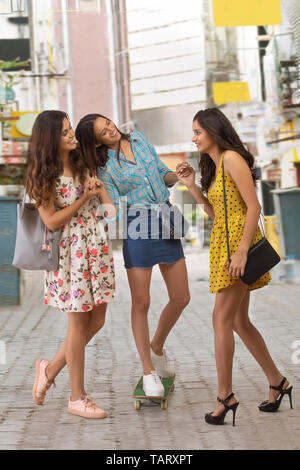 Women having fun standing on street holding each other - Stock Image