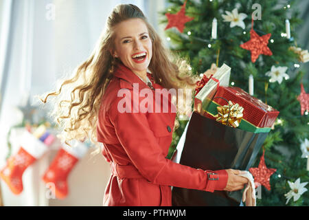 Portrait of cheerful young woman in red trench coat with shopping bag full of Christmas present boxes near Christmas tree - Stock Image