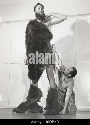 Eight foot man measured for custom tailored fur suit - Stock Image