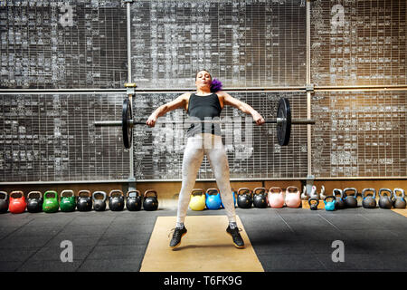 Young woman athlete doing the snatch with a barbell snatching it off the ground to lift it above her head in a single movement seen straining with eff - Stock Image