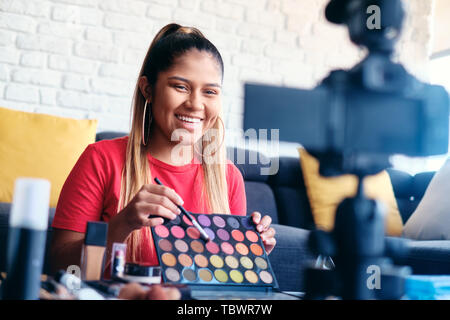 Happy girl at home speaking about make up in front of camera. Video blogger recording message for social media and internet - Stock Image