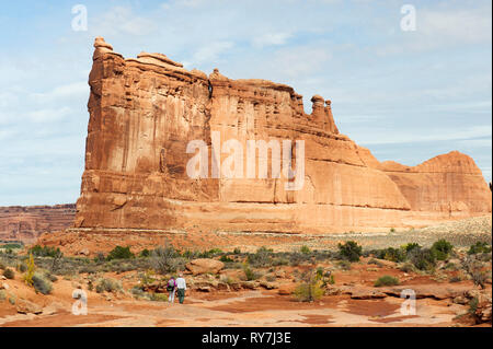 Two hikers approaching a gigantic sandstone formation known as the Tower of Babel on Park Avenue trail in Arches National Park, Utah, USA. - Stock Image