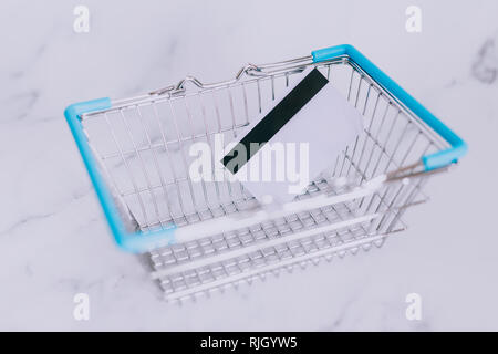 payment card and empty shopping basket, concept of shopping and expenses - Stock Image