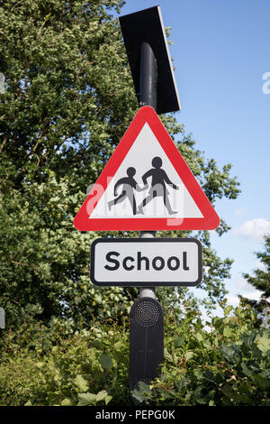Solar-powered road sign with lights outside of school warning of school crossing Kingsley Cheshire June 2018 - Stock Image