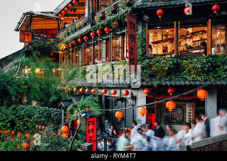 Jiufen, Taiwan - November 7, 2018: Tourists walk through the famous stair in front of the old teahouse decorated with Chinese lanterns, Jiufen Old Str - Stock Image
