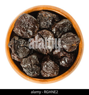 Prunes, dried plums in wooden bowl. Uncooked, dehydrated, pitted fruits of Prunus domestica with black color, used as snack. Isolated macro photo. - Stock Image
