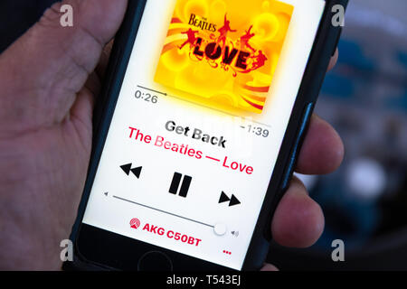 In this photo illustration, somebody is listening to The Beatles music on a smartphone. The screen shows 'Get Back' song title and the cover of the al - Stock Image