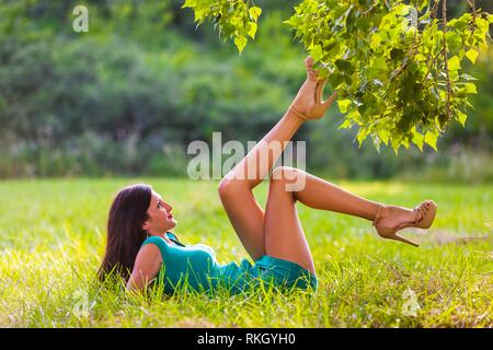 Beautiful teenager lying on greenfield in nature with legs holding in air upwards young woman legs heels - Stock Image