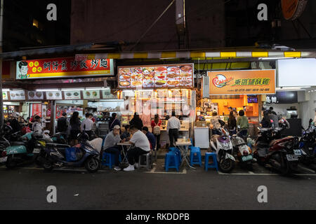 Taipei residents buy food from food stall vendors at a local food night market in Daan District in Taipei, Taiwan, to eat there or to take away. - Stock Image