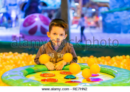 Kownaty, Poland - January 6, 2019: Young boy sitting by a air blowing machine with plastic orange balls on a playground in the Majaland indoor attract - Stock Image
