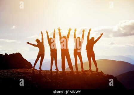 Five happy friends with raised arms - Stock Image