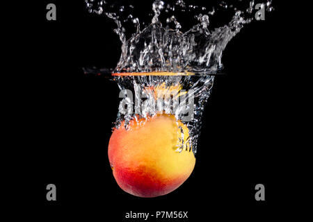 A peach splashing into water on a black background. - Stock Image
