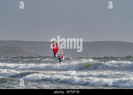 Marazion, Cornwall, UK. 8th December 2018. UK Weather. Yellow weather warnings are in place in Cornwall for gale force winds and flooding. Sailboarders were out on the seas at Marazion making the most of the strong winds. Credit: Simon Maycock/Alamy Live News - Stock Image