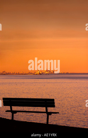 Empty bench overlooking the lake or ocean during sunset or sunrise.  Far away is the city of toronto - Stock Image