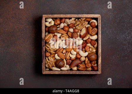 mix of nuts on a dark brown background. view from above. copy space - Stock Image