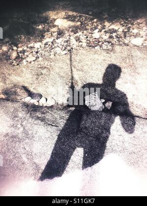 Shadow of a fisher man - Stock Image