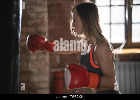 An aggressive woman boxer hitting the punching bag in the gym on the training - Stock Image