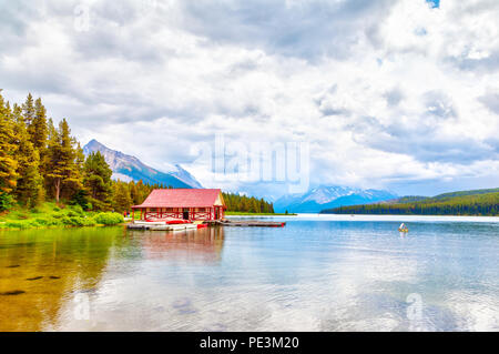 Colorful canoes lie on the boat house dock at Maligne Lake in Jasper National Park, Alberta, Canada. The lake is famous for the surrounding peaks and  - Stock Image