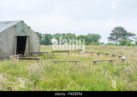 Field tent with circle of small bench seating. Metaphor for meeting place, sitting round in a circle, circular discussions, etc. - Stock Image